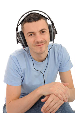 young handsome man listening to music in headphones. isolated Stock Photo - 9225186