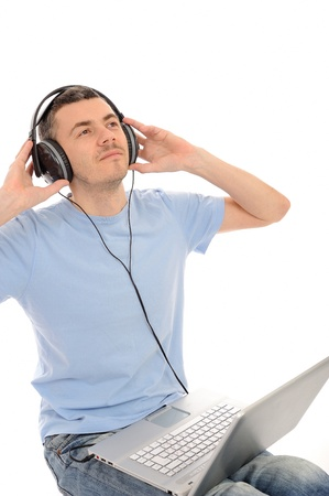 young handsome man listening to music in headphones from computer. isolated photo