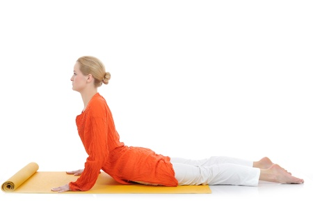 series or yoga photos. young woman in cobra pose on yellow pilates mat photo