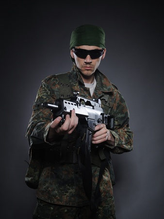 one armed: Young soldier in camouflage and ammunition with a gun. studio shot Stock Photo