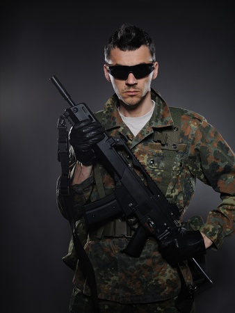 Young soldier in camouflage and ammunition with a gun. studio shot photo