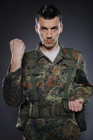 portrait of soldier in camouflage and ammunition fighting. studio shot Standard-Bild