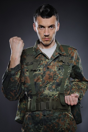 portrait of soldier in camouflage and ammunition fighting. studio shot photo