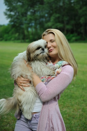 shih: Pretty casual woman with cute little shih tzu dog outdoors in a park Stock Photo