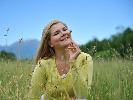 Pretty healthy summer woman outdoors on green field in Alps enjoying freedom. Switzerland Stock Photo - 9568660