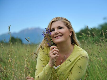 Beautiful natural woman with pure healthy skin outdoors on spring field. Switzerland Stock Photo - 9568661