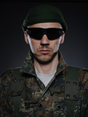 portrait of soldier in camouflage and ammunition . studio shot photo