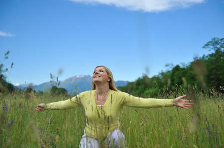 Pretty healthy summer woman on green field in Alps enjoying freedom. Switzerland Stock Photo - 9678357