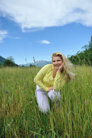 Pretty healthy summer woman outdoors on green field in Alps enjoying freedom. Switzerland photo