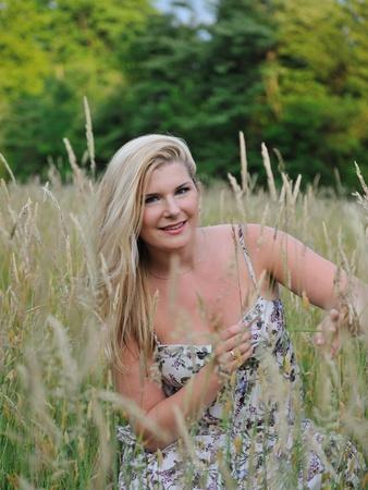 Pretty summer woman on yellow wheat field on vacation photo