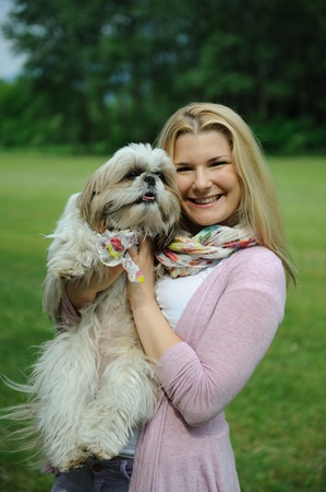 Pretty casual woman with cute little shih tzu dog outdoors in a park Stock Photo - 9802455