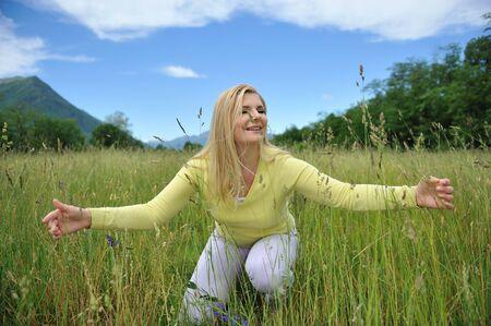 Pretty healthy summer woman outdoors on green field in Alps enjoying freedom. Switzerland photo