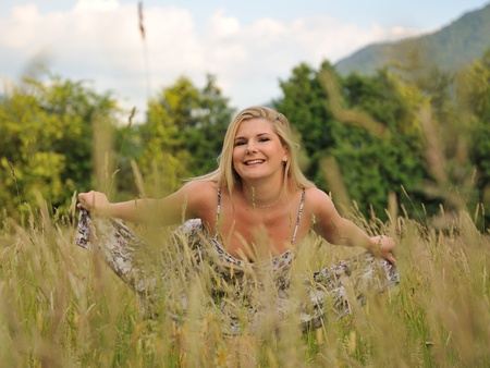 Pretty summer woman on yellow wheat field in countryside relaxing Stock Photo - 9802232