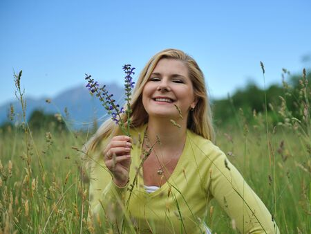 Beautiful natural woman with pure healthy skin outdoors on spring field. Switzerland Stock Photo - 10476732