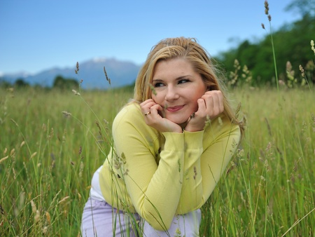 Beautiful natural woman with pure healthy skin outdoors on spring field. Switzerland Stock Photo - 10476734