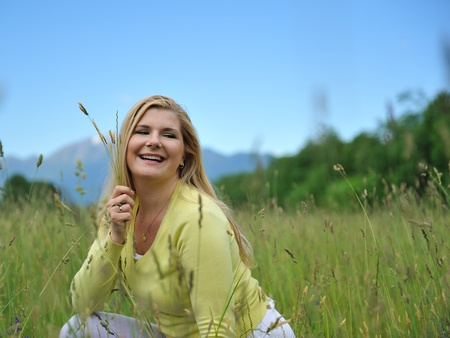 Beautiful natural woman with pure healthy skin outdoors on spring field. Switzerland Stock Photo - 11079835