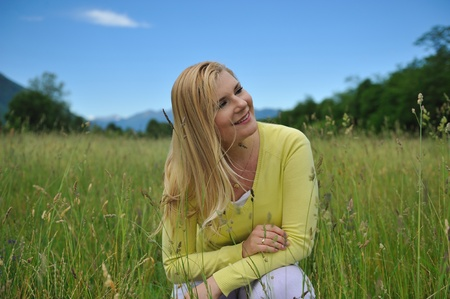 Pretty healthy summer woman on green field in Alps. Switzerland Stock Photo - 11079844