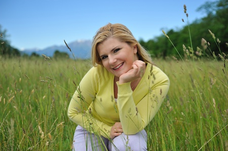 Beautiful natural woman with pure healthy skin outdoors on spring field. Switzerland Stock Photo - 11257415