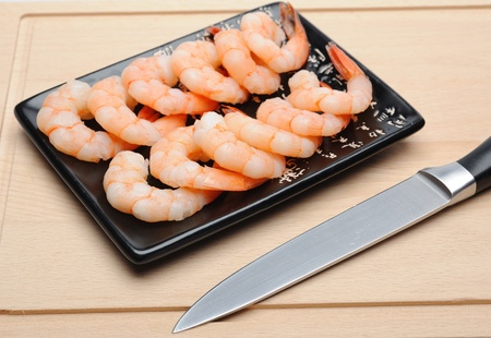 fresh shrimps on wooden board isolated. sushi ingredient photo