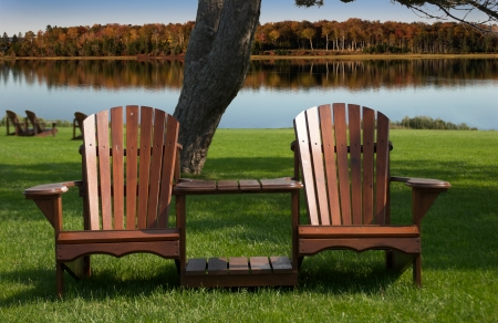 Muskoka - Adirondack chairs in front on still lake with fall colours in the background