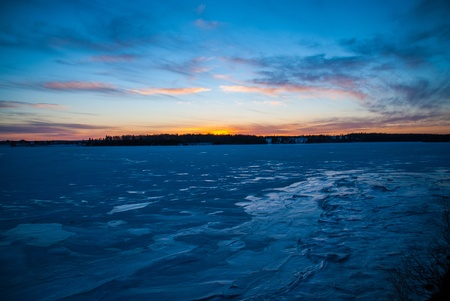 Frigid frozen wind swept lake in cold blue cast with yellow sunset