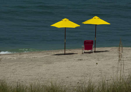 Two Yellow Beach Umbrellas with pink chair Stock Photo - 5237038