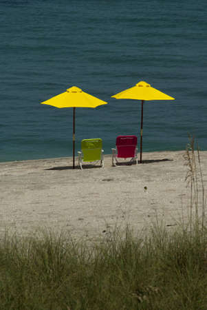 Verticle Two Yellow Beach Umbrellas with pink and green chair photo