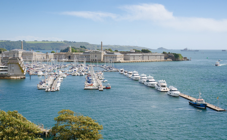 PLYMOUTH, UK. August 19th 2017. Plymouths Royal William Yard and Breakwater, viewed from the hilltop of Mount Wise, green trees in the foreground. The Willaim Yard has become a major draw for tourists to the city of Plymouth over the last few years.
