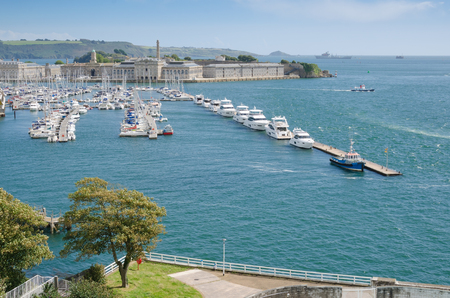 PLYMOUTH UK. August 19th 2017. Plymouths Royal William Yard and Breakwater viewed from the hilltop of Mount Wise green trees in the foreground. The Willaim Yard has become a major draw for tourists to the city of Plymouth over the last few years. Editorial