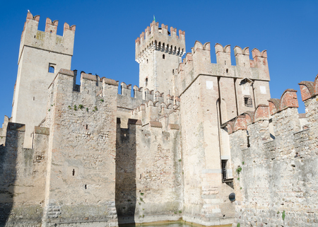 SIRMIONE, ITALY. October 23rd 2017. The Scaliger Castle - a 13th Century defensive fortification - dominates the skyline of Sirmione and draws tourists into the town, even in Autumn.