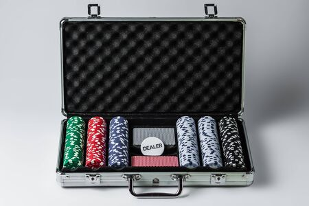 Suitcase with poker set on a light background Banque d'images - 135168328
