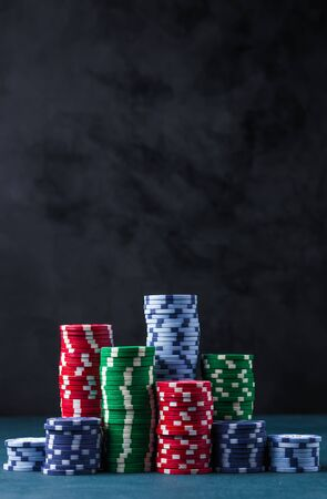 stack of poker chips on a blue table on a black background Banque d'images - 135168323