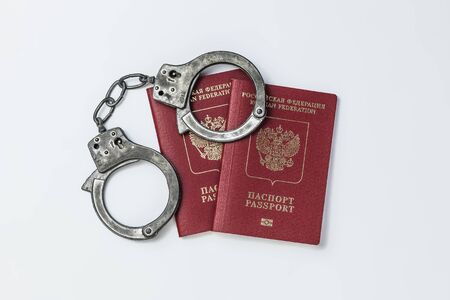 Two Russian passports with handcuffs on a white background Banque d'images - 134842826