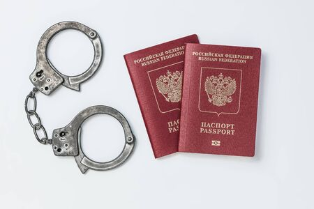 Two Russian passports with handcuffs on a white background