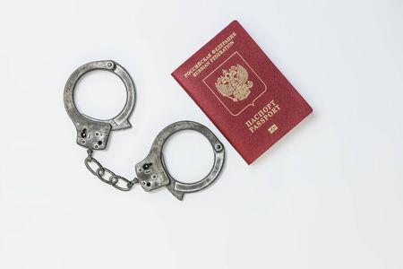 Handcuffs next to a Russian passport on a white background Banco de Imagens