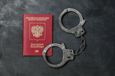 Russian passport with handcuffs on black background