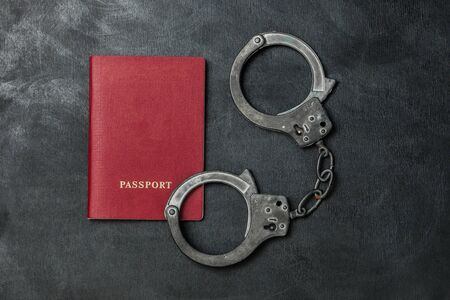 Passport with handcuffs on black background Banque d'images - 134842912