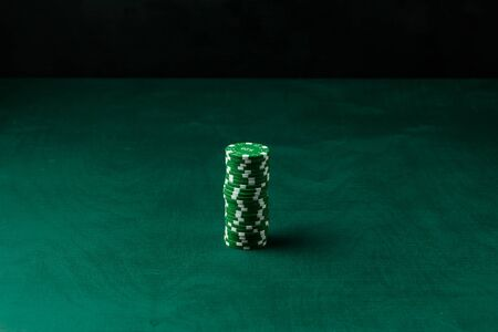 Stack of poker green chips on the table on a black background Banque d'images - 134842957
