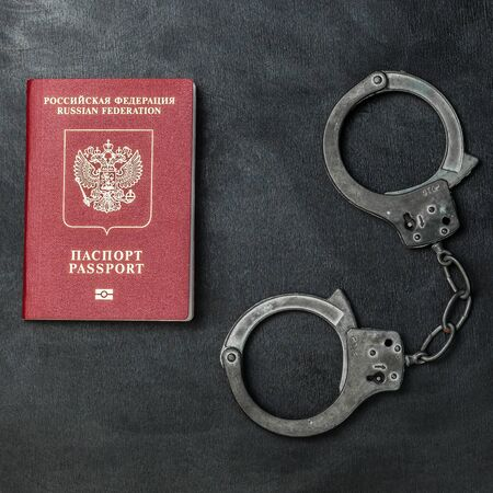 Russian passport with handcuffs on black background Banque d'images - 134843053
