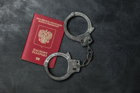 Russian passport with handcuffs on black background Banque d'images - 134843055
