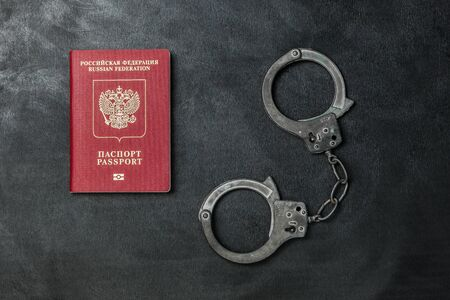 Russian passport with handcuffs on black background Banque d'images - 134843126