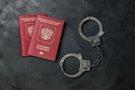 two Russian passports on a black background with handcuffs Banque d'images - 134843139