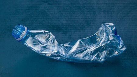 Plastic bottle on dark blue background. The concept of ecology. 免版税图像