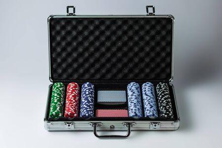 Suitcase with poker set on a light background Foto de archivo