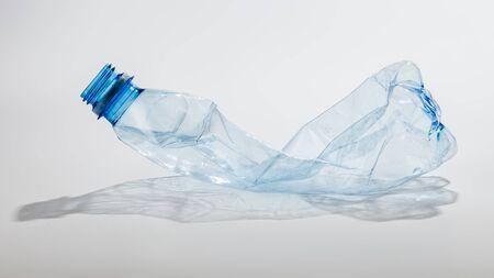 Crumpled plastic bottle on a light background Imagens