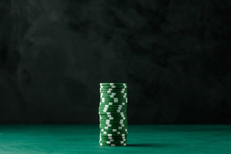 Stack of poker green chips on the table on a black background