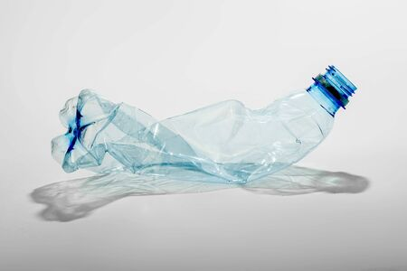 Crumpled plastic bottle on a light background. The concept of ecology