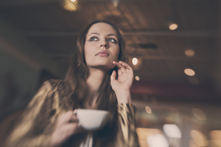 coffee shop: A young beautiful girl with a cup of tea, cappuccino toning