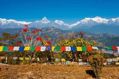 Tibetan prayer flags with view of Phewa lake and Annapurna mountain range from World Peace Pagoda in Pokhara, Nepal