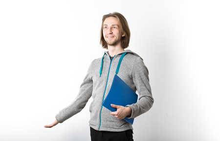 Portrait of young man with long blond hair holding a blue folder in his hands, white background Stock Photo